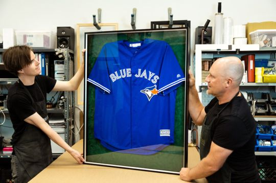 2 men displaying a framed jersey