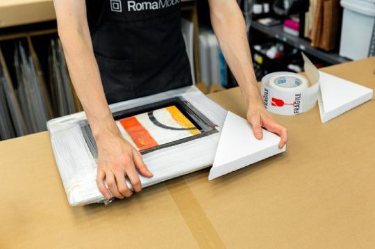 a person packaging a frame