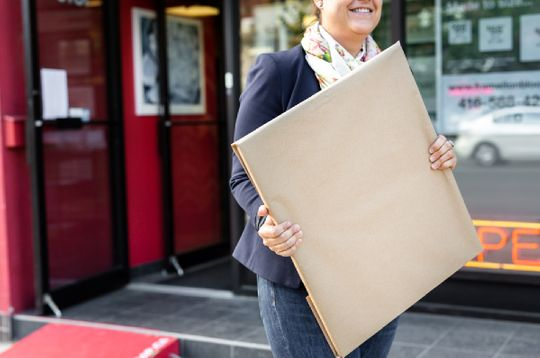 A smiling woman carrying a packaged frame